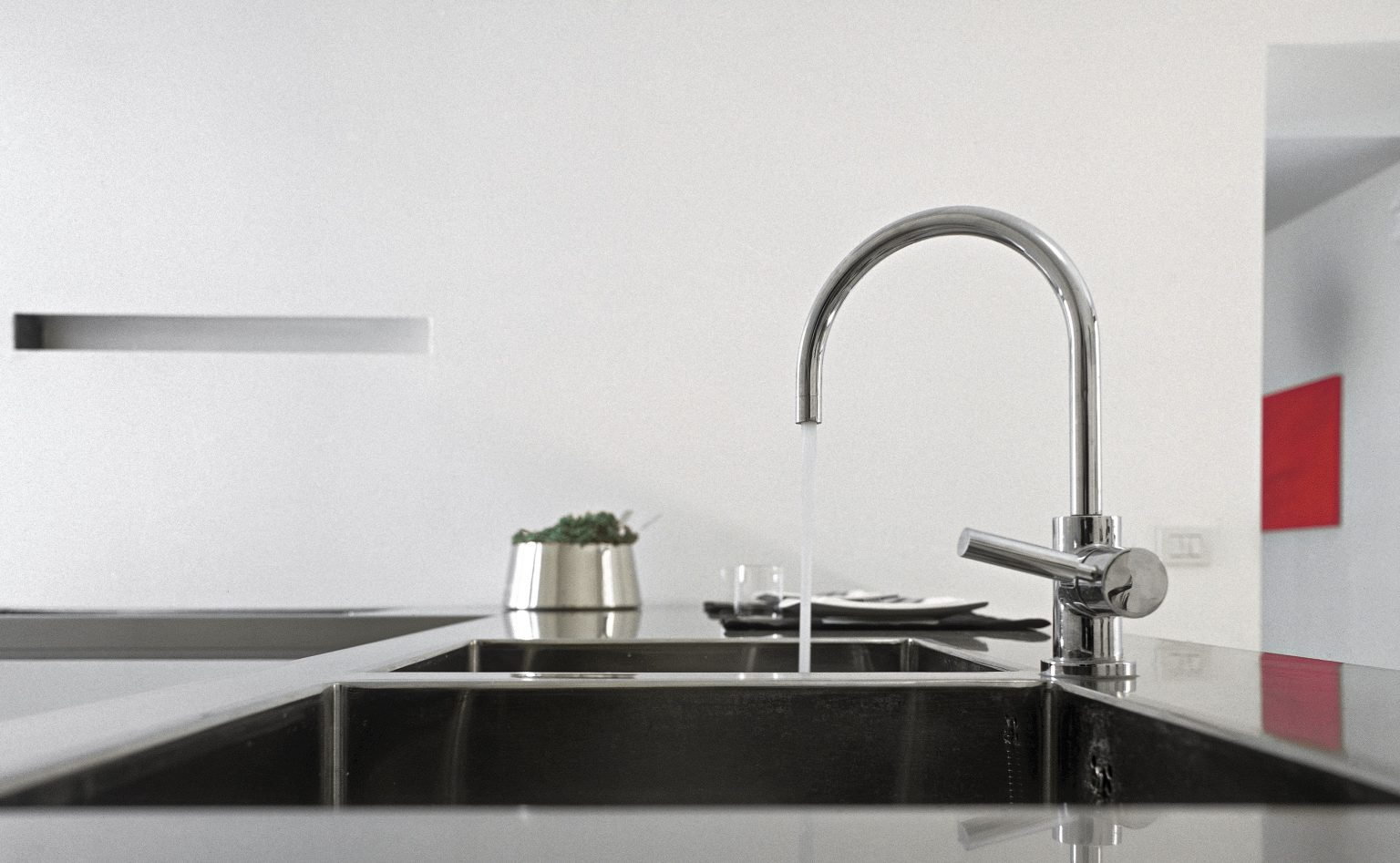 detail of steel faucet in a modern kitchen with steel worktop